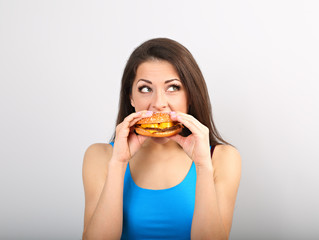 Thinking funny excited woman eating burger on blue background. Closeup portrait