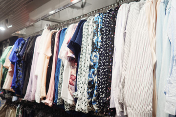 Elegant light blouses hanging on metal rack in modern clothes shop