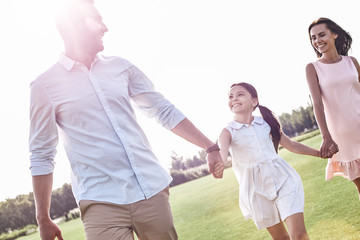Family walk. Family of three walking on grassy field laughing ch