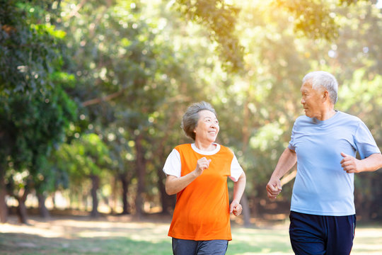 happy Senior couple running in the park