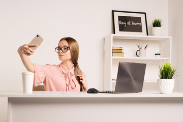 Portrait of a playful young girl taking selfie with mobile phone while sitting with laptop computer