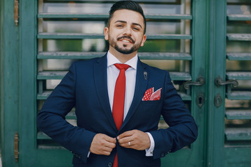 Beautiful bearded turkish man standing by the wall in a blue suit