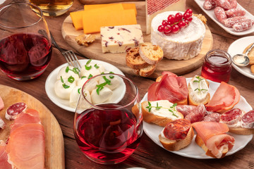 Wine tasting and pairing. A wineglass with sandwiches and a cheese platter on a dark wooden background