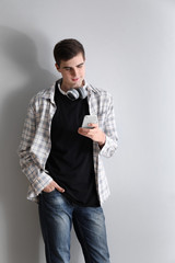 Handsome young man with mobile phone and headphones on light background