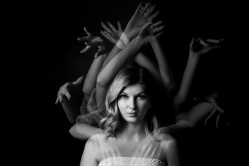 Stroboscopic photo of young woman with moving hands on dark background