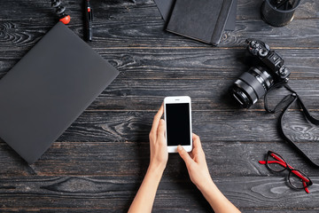 Female photographer with mobile phone at workplace, top view