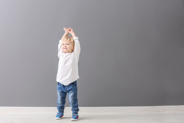 Portrait of cute little boy near grey wall