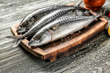 Board with tasty raw mackerel fish on wooden table Wall mural