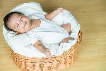 Baby infant boy lying on wood basket top view