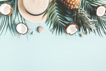 Summer composition. Tropical palm leaves, hat, coconut, pineapple on pastel blue background. Summer concept. Flat lay, top view, copy space