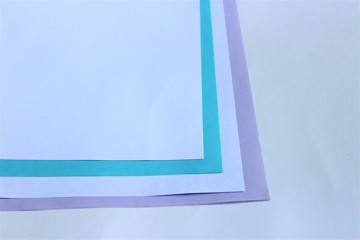 White and colored sheets of paper on white background. Cool shades.