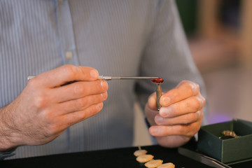 Jeweller examining gemstone in workshop, closeup