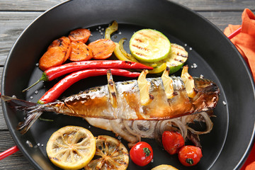 Frying pan with tasty mackerel fish and vegetables on table