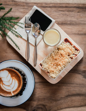 Berry and apple crumble on wood tray with hot latte coffee