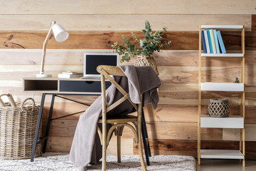 Interior of modern room with comfortable workplace near wooden wall