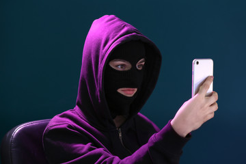 Female hacker in mask and with mobile phone on color background