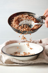 Pouring of tasty buckwheat from frying pan into bowl on table