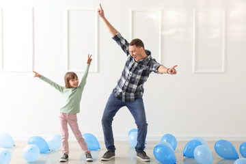 Father and his cute little daughter dancing in room with balloons