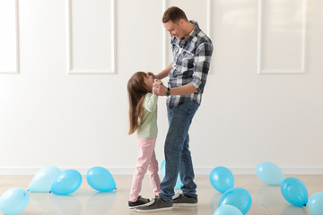 Cute little girl dancing on her father's feet in room with balloons