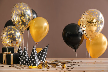Balloons, gifts and party hats on table against color background