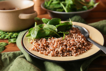 Bowl with tasty boiled buckwheat on table
