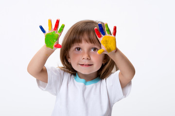 Happy smiling beautiful little girl with her colorful hands in the paint isolated on white background