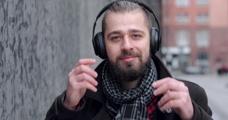 fe9fd22c8df 0 05 Bearded man look at camera and wear black head phones outside
