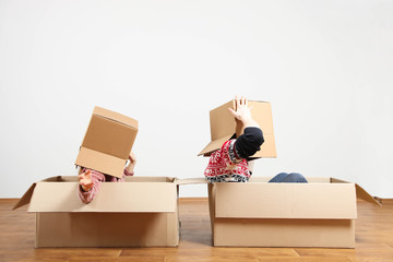 couple sit in boxes in new apartment.
