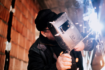 Industrial portrait of worker with protective mask welding metal on site