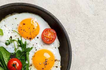 Border with fried eggs with herbs and cherry tomatoes on pan