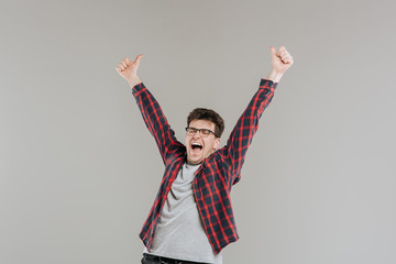 smiling and excited man, raise his hands up, thumb up, OK OK, in glasses,  checkered shirt,  gray background, isolated, positive facial emotion,  copy space