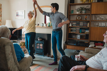 Senior Woman Dancing with Grandson at Home