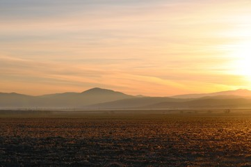 Spectacular golden sunrise on cleaned agricultural field with smooth hills on horizon in Khakassia, Russia