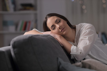 Woman sleeping on a couch in the night at home