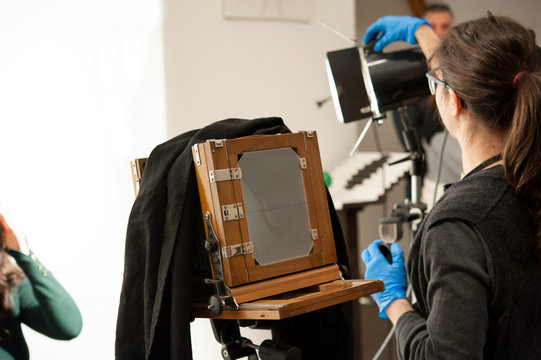 Photographer woman sets the ligths for portrait studio shooting. Large format camera in the foreground.