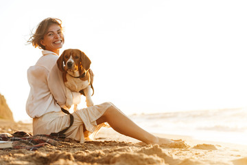 Image of positive woman 20s hugging her dog, while sitting on sand by seaside Wall mural