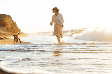 Image of lovely woman 20s running with her dog, by seaside in the morning