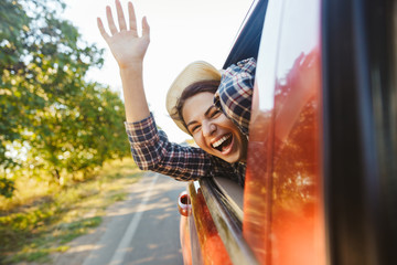 Image of happy woman 20s wearing straw hat laughing and waving hand out of the window, while riding in car