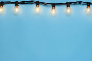 Light bulb string light on blue background copy-space