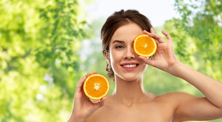 beauty and people concept - smiling young woman with oranges over green natural background