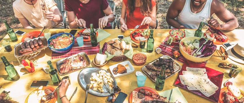 Group of happy friends eating and drinking beers at barbecue dinner in backyard garden - Focus on center table - Summer lifestyle, food and friendship concept