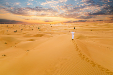 Arabic man with traditional emirates clothes in the desert, sunset.