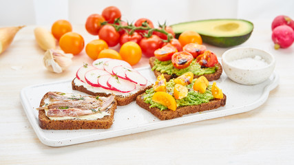 Set of smorrebrods with fish, anchovies, avocado, tomatoes, radish. Side view, white background