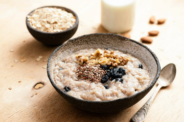 Oatmeal porridge with raisin and seeds in bowl on wooden table. Tasty healthy breakfast. Morning vegan meal