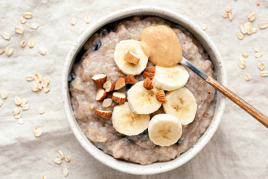 Bowl of oatmeal porridge with banana and peanut butter over linen background. Top view. Healthy vegan breakfast