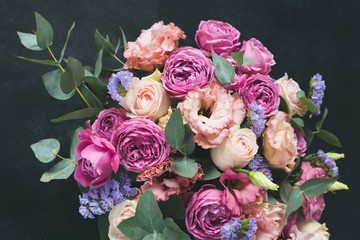 Bouquet of peonies and roses decorated with eucalyptus. Wedding or birthday flowers on black background