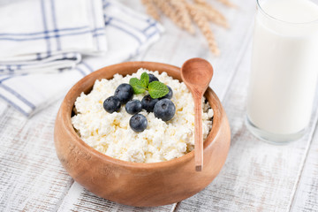 Tvorog or cottage cheese in wooden bowl, bottle of cow milk and wheat ears on rustic wooden table background. Healthy dairy products rich in Protein and Calcium