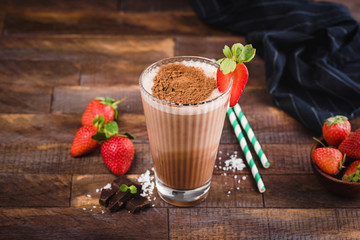 Chocolate milkshake or cocktail in glass cup on brown wooden background. Protein milkshake with strawberry