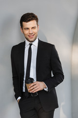 Handsome young businessman in formal clothes outdoors at the street holding coffee.