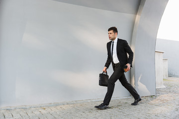 Serious young businessman in formal clothes outdoors at the street holding coffee.
